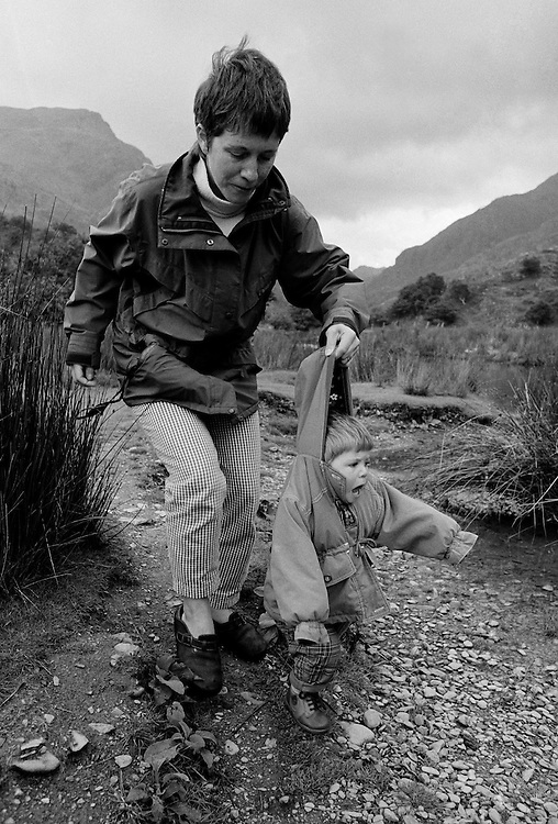 """""""First shoes in Wales."""" An eleven month-old infant tries to walk in her first pair of proper rigid shoes whilst on holiday in Snowdonia, North Wales UK. Tentatively taking a few unconfident steps the young girl  cries out in surprise, almost falling over. Her mother instinctively grabs her coat hood before she topples into into the pebbles and soft mud of a river bed which would soil her clean clothes. We see a mother preventing her daughter from getting dirty and from hurting herself, a fast reaction to stop injury on a small child. This is from a documentary series of pictures about the first year of the photographer's first child Ella. Accompanied by personal reflections and references from various nursery rhymes, this work describes his wife Lynda's journey from expectant to actual motherhood and for Ella - from new-born to one year-old."""