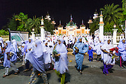11 JULY 2013 - PATTANI, PATTANI, THAILAND:  Women file out of Pattani Central Mosque in Pattani, Thailand, Thursday night after Ramadan services. The mosque is one of the busiest in south Thailand. About 15,000 people attend nightly Ramadan services in the mosque. Ramadan is the ninth month of the Islamic calendar, and the month in which Muslims believe the Quran was revealed. Muslims believe that the Quran was sent down during this month, thus being prepared for gradual revelation by Jibraeel (Gabriel) to the Prophet Muhammad. The month is spent by Muslims fasting during the daylight hours from dawn to sunset. Fasting during the month of Ramadan is one of the Five Pillars of Islam.     PHOTO BY JACK KURTZ