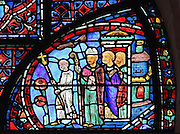 At the gates of Constantinople, a group of people await the arrival of the relics of St Stephen. A clerk holds the processional cross and bishop Eusebius, wearing his mitre and holding a book, stands in wait. Section of the Procession, 1220-25, from the Life of St Stephen and transferral of his relics window in the ambulatory of Chartres Cathedral, Eure-et-Loir, France. This window, unusually dominantly red in colour, tells the story of the life of St Stephen, the first Christian martyr, who died c. 36 AD and whose relics are held at Chartres. It is situated in the chapel dedicated to martyrs. Chartres cathedral was built 1194-1250 and is a fine example of Gothic architecture. Most of its windows date from 1205-40 although a few earlier 12th century examples are also intact. It was declared a UNESCO World Heritage Site in 1979. Picture by Manuel Cohen