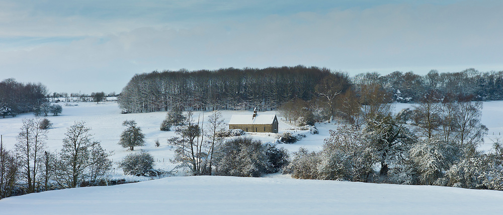 Quaint 13th Century chapel in snow-covered Windrush valley at Widford in the The Cotswolds, England -  RESERVED USE