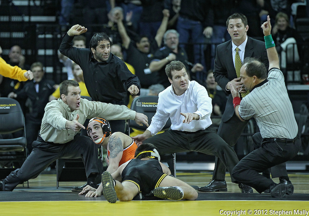 January 07, 2011: Iowa's Tony Ramos scores a takedown on Oklahoma State's Jordan Oliver as Iowa assistant coach Terry Brands and head coach Tom Brands look on during the 133-pound bout in the NCAA wrestling dual between the Oklahoma State Cowboys and the Iowa Hawkeyes at Carver-Hawkeye Arena in Iowa City, Iowa on Saturday, January 7, 2012. Ramos won 4-3.