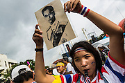 24 NOVEMBER 2013 - BANGKOK, THAILAND:     A royalist anti-government protestor holds up a photo of Bhumibol Adulyadej, the King of Thailand, during a protest in Bangkok. More than 400,000 people packed onto Ratchdamnoen Ave in Bangkok Sunday, continuing an anti-government protest that started weeks ago over a blanket amnesty bill passed by the Thai Parliament. The amnesty bill was defeated in the Thai Senate and the protest morphed into a general protest against the government. The protestors are allied with the Thai Democrat party, the opposition party in parliament. Tens of thousands of pro-government Red Shirts have come to Bangkok to defend the government and are rallying in a different part of the city. Police have warned of clashes between the two groups but as of Sunday evening no problems had been reported. The protestors allege that the amnesty would allow fugitive former Prime Minister Thaksin Shinawatra to return to Thailand.        PHOTO BY JACK KURTZ