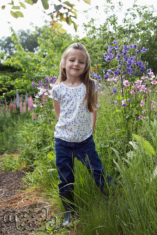Girl (5-6) standing in garden portrait