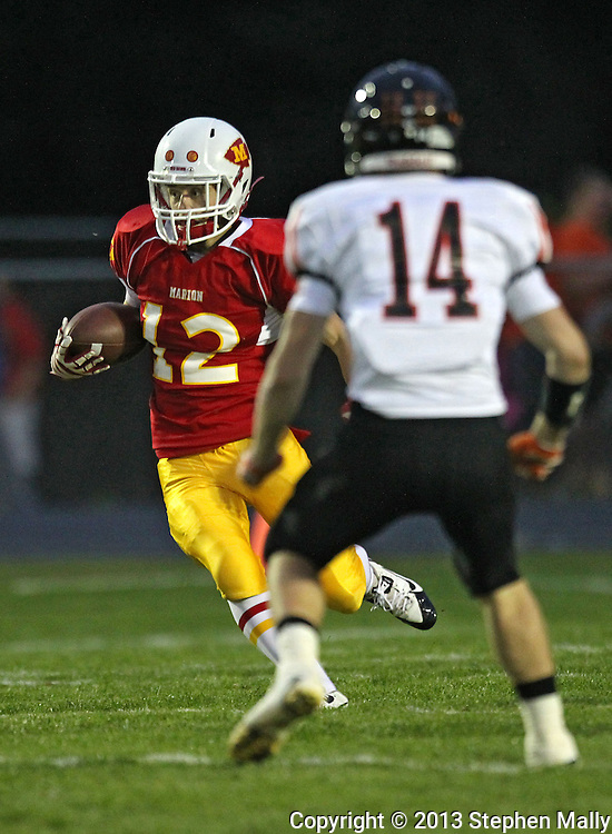 Marion's Austin Brown (12) tries to avoid Washington's Jeff Knupp (14) on a run during their game at Thomas Park Field in Marion on Friday, September 20, 2013.