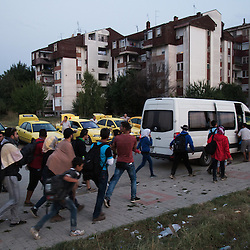 Refugees rush to border a bus in Gevgelija, Macedonia on August 26, 2015. After crossing the border into Macedonia, refugees make their way to the border with Serbia by train, bus or taxi, to continue north to other European states.