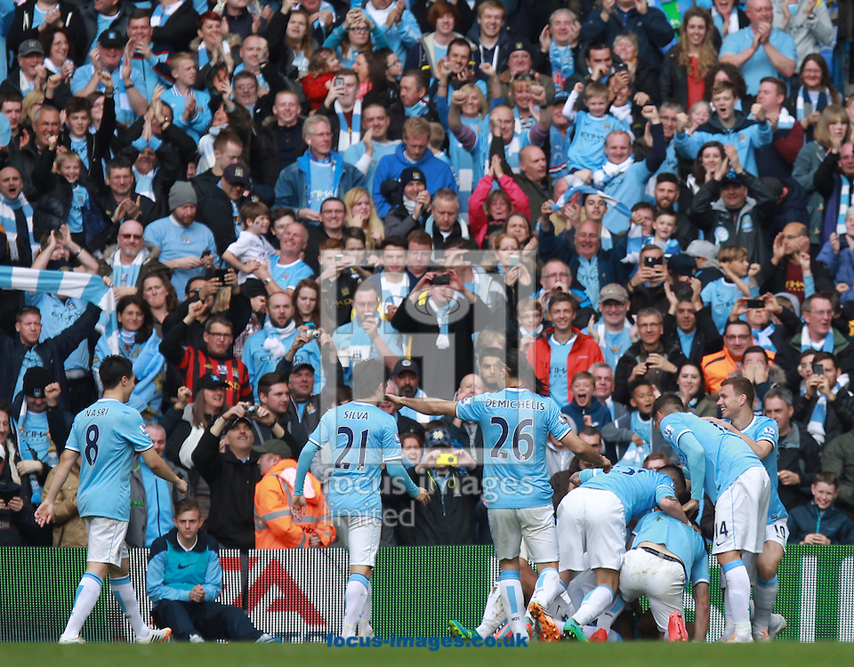 Vincent Kompany of Manchester City is mobbed by team-mates after scoring the second goal against West Ham United during the Barclays Premier League match at the Etihad Stadium, Manchester<br /> Picture by John Rainford/Focus Images Ltd +44 7506 538356<br /> 11/05/2014