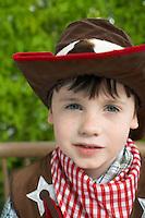 Boy (7-9) wearing cowboy costume portrait close-up