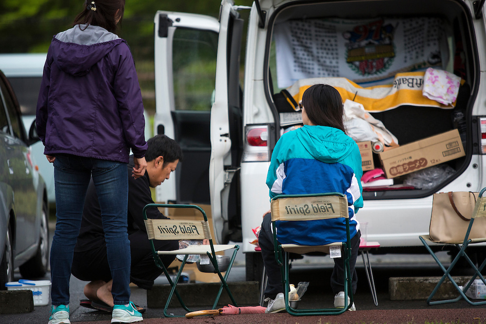 KUMAMOTO, JAPAN - APRIL 21: A family, survived from earthquake is seen in the car park early morning on April 21, 2016 in Mashiki Gymnasium parking area, Kumamoto, Japan. Over thousands of evacuees sleep in the car and survivors are facing health threat, health experts says, 20 people diagnosed in Mashiki, one has died and 2 are in critical condition.<br /> As of April 45 people were confirmed dead after strong earthquakes rocked Kyushu Island of Japan. Nearly 11,000 people are reportedly evacuated after the tremors Thursday night at magnitude 6.5 and early Saturday morning at 7.3.<br /> <br /> Photo: Richard Atrero de Guzman
