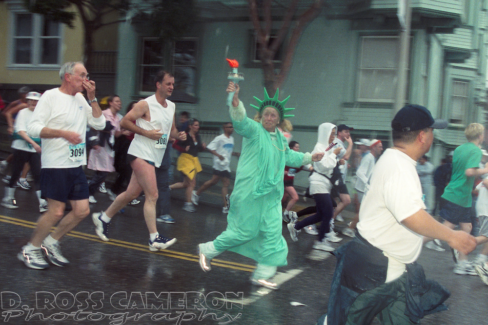 A woman dressed as the Statue of Liberty crests the Hayes Street hill during the 91st Bay to Breakers Sunday, May 19, 2002 in San Francisco. (Photo by D. Ross Cameron)