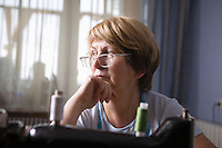 Mature woman sits leaning on elbow at sewing machine