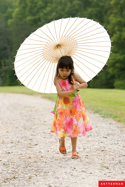 A cute little girl walks down a path with her umbrella.