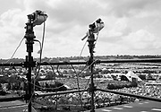 Two cameras on scaffolding view over hundred of tents and a stage below. Glastonbury 2000
