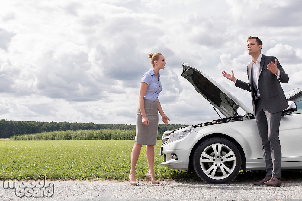 Full length of business couple having argument by broken car at countryside
