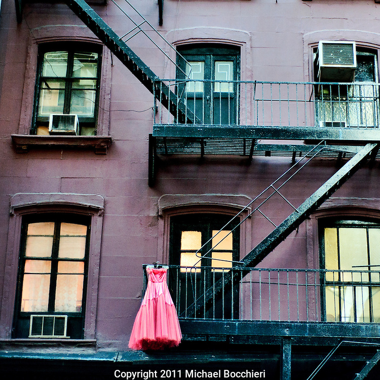 NEW YORK, NY - December 16:  A pink ball gown dress hangs from a building's fire escape on December 16, 2011 in NEW YORK, NY.  (Photo by Michael Bocchieri/Bocchieri Archive)
