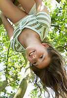 Young girl hanging upside down from tree low angle view