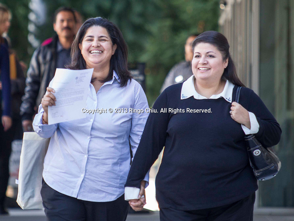 Yamileth Escobar, right, and Maria de los Angeles Dominguez, a bi-national lesbian Latina couple (Yamileth, a U.S. Citizen, is of Salvadoran decent while Maria is an immigrant from Mexico), leave the Federal Building after  an immigration green card interview on Wednesday November 6, 2013 in Los Angeles, California.  Yamileth and Maria became the first Hispanic same-sex female couple to receive an immigration green card interview, also the first female same-sex couple to legally marry in the state following the State Supreme Court's 2008 decision. (Photo by Ringo Chiu/PHOTOFORMULA.com)