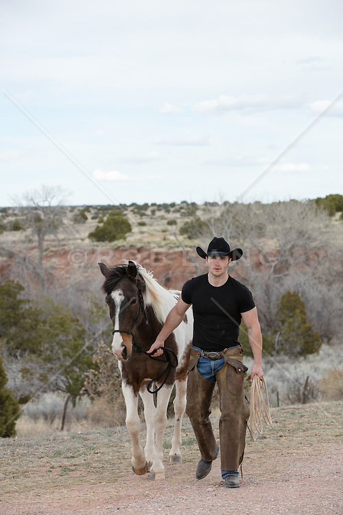 good looking cowboy on a ranch with a horse