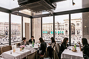 Milan, GIACOMO, Risotrante Arengario . The restaurant Giacomo Arengario is located in the eponymous building located in Piazza Duomo, where Museo del Novecento has been located since December 2010. Created as a tribute to the artistic context in which it is located, Giacomo Arengario is characterized by a clear reference to the avant-garde and unique style of the early twentieth century, maintaining a continuous dialogue with the works on display inside the rooms of the museum. The Restaurant is situated along the entire circular ramp rising from the ground floor to the third floor, a space that offers different services such as cafe, aperitif and dinner adapting on needs as different as the areas that characterize it. It features a hall, low tables, chairs and couches, a bar composed of different elements featuring mirrored black lacquered wood, a dining room with panelled walls of gilded wood and vintage mirrors, a coffered ceiling and a gallery opening into the kitchen with red lacquer from the thirties and a counter where you can sit. Particular attention has been paid to Outdoor seating located within the large loggia overlooking Piazza del Duomo, an iron and glass structure that offers a breathtaking view and the perfect spot from which to spy on the Duomo and the Piazza.