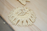 carved and decorated bread in dove nest shape on wooden counter before ovening, Sardinian bread sculpture, the Pani Pintau