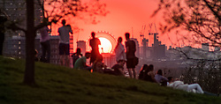 © Licensed to London News Pictures. 19/04/2018. London, UK. Members of the public watch from a high point in Greenwich Park in London as the sun sets behind the London Eye, on a warm spring evening. Photo credit: Micheal Tomas/LNP