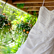 Photo of a bridal gown hanging from the rafters of a porch.