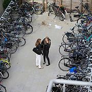 Nederland Rotterdam 23-09-2009 20090923 Serie over onderwijs Vriendinnen luisteren samen muziek via mp3 speler tussen de fietsenrekken op het schoolplein.                                           .Foto: David Rozing