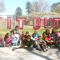 """HOULKA SCHOOLS PUT IT OUT<br /> (Courtesy Photo)<br /> Students from Houlka Attendance Center, School Nurse Chandra Warren and MS Tobacco Free Coalition Project Director Stephanie Collier participated in this year's """"Kick Butts Day"""" event. Students participating in this event placed cups in a chain-linked fence, located on the school property, which spelled out the phrase """"PUT IT OUT"""" in reference to second-hand smoke."""