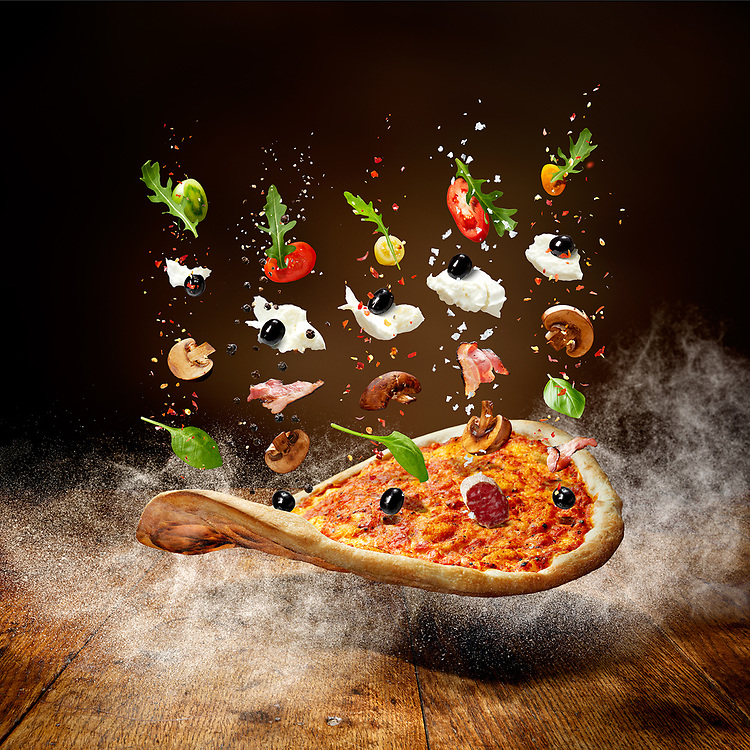 Pizza ingredients falling onto a pizza base.