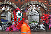Pedestrians passing through brick walls with horseshoe arch and window and with colorful spray paint graffitis, Shoreditch, London, UK. Picture by Manuel Cohen