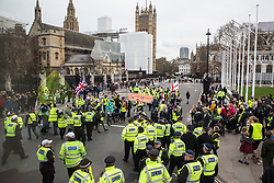 London, UK. 9th March, 2019. Metropolitan Police officers prevent pro-Brexit activists from Yellow Vests UK from blocking the road in Parliament Square. At least one activist was detained by police officers.