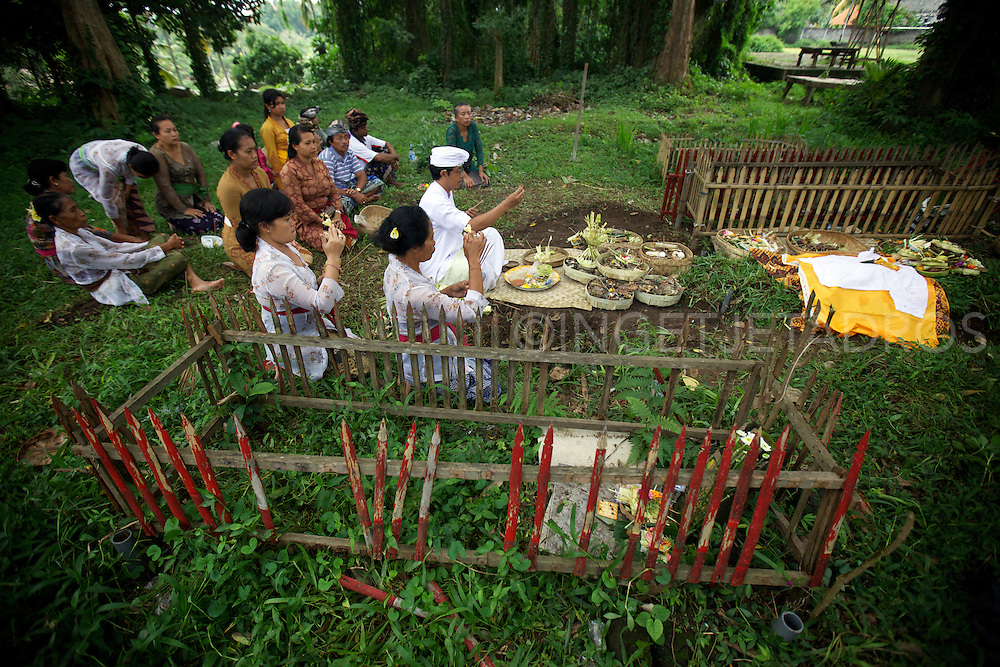 Woman sprinkling water and performing rituals next to a grave.<br /> When a Balinese dies, it is believed that he must undergo certain rituals in order for his spirit to be released.<br /> The most important of the rituals is that of cremation, but it is so costly that many people either delay the ceremonies or go into massive debt to perform the rituals associated with the cremation.<br /> Before cremation, the body must be prepared for burial.<br /> The corpse is than buried for a certain period of time but no longer than 3 years.<br /> On the appointed time of the cremation, the family (or if several families cannot afford the cremation ceremony and rituals, a group cremation will occur and a cremation tower will be build and elaborate offerings will be prepared.<br /> Ubud, Bali 2013<br /> &copy;Ingetje Tadros www.ingetjetadros.com