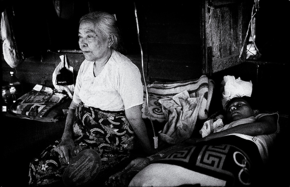 An elderly woman cares for her HIV positive daughter at the HIV & Aids Clinic on the outskirts of Yangon (Rangoon) Myanmar (Burma) January 2012
