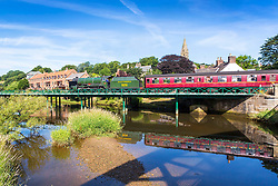 """© Licensed to London News Pictures. 18/07/2018. Ruswarp UK. 1934 Locomotive 926 """"Repton"""" travels on the North Yorkshire Moors Railway across the river Esk in the picturesque village of Ruswarp, north Yorkshire this morning. Photo credit: Andrew McCaren/LNP"""