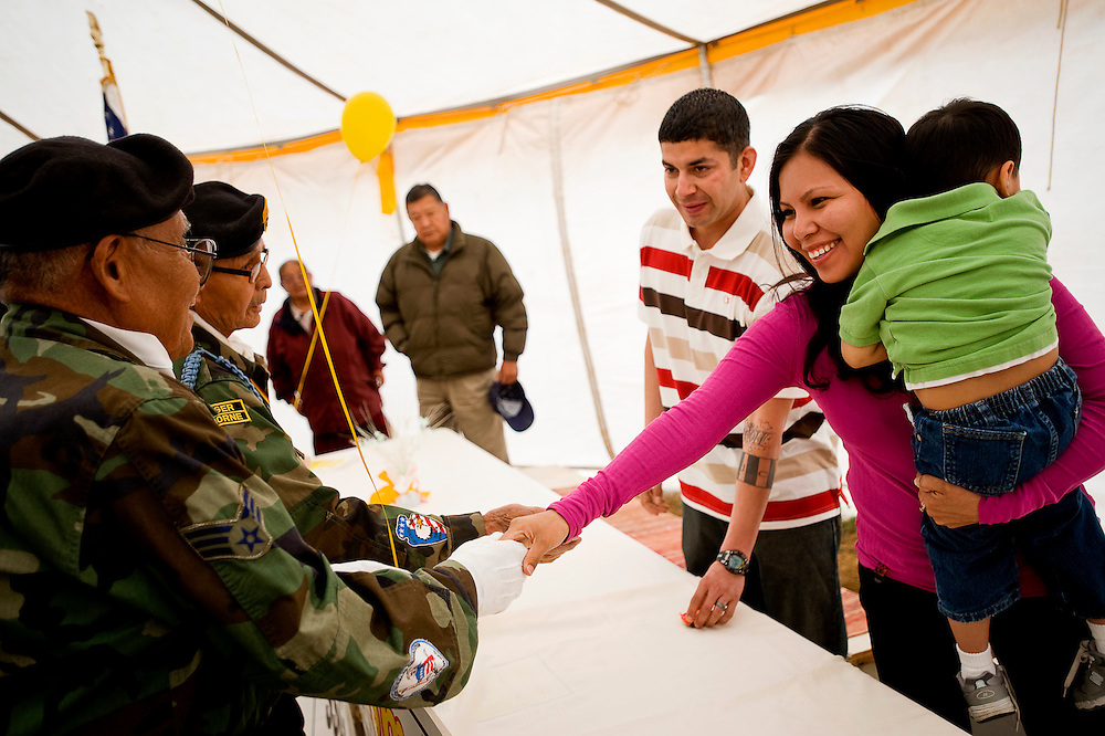 033110        Brian Leddy.Alvina Espinoza and her husband Juan shake hands with member of the Tohatchi Veteran's Association on Wednesday during a homecoming gathering in Pine Hill. The Espinoza's both recently finished up tours of duty in Iraq and Afghanistan and received a warm welcome from family and friends.