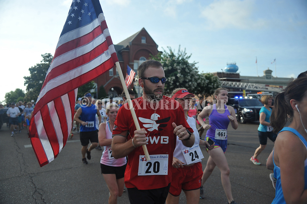 Noah Miller carries the U.S. flag while running in the Stars and Stripes 5K in Oxford, Miss. on Monday, July 4, 2016. The race is sponsored by the Oxford Lafayette Humane Society.