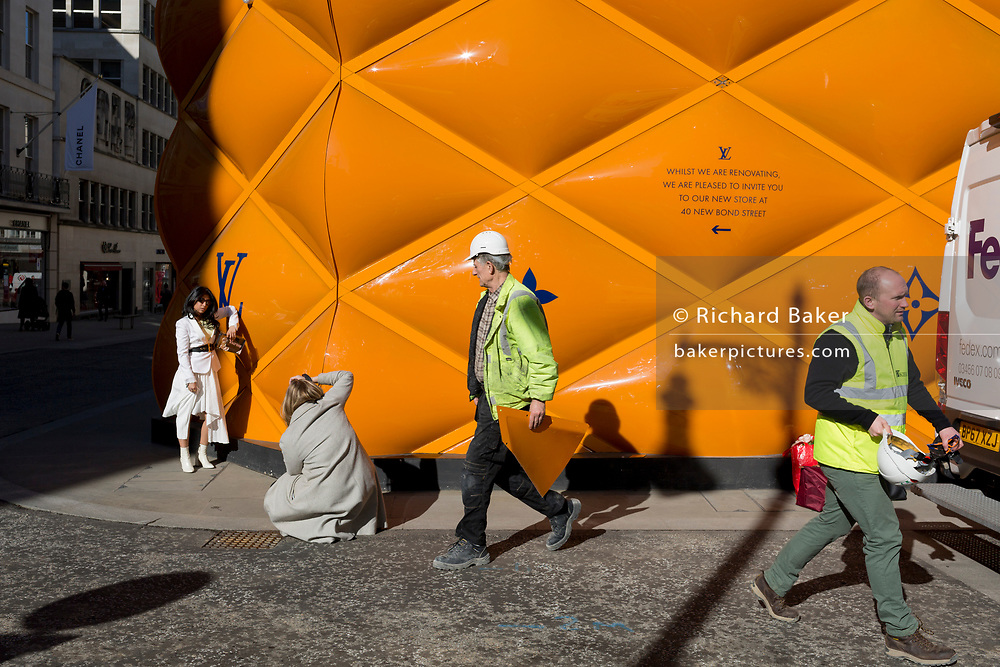 A fashion model is photographed against the temporary renovation hoarding of luxury brand Louis Vuitton in New Bond Street, on 25th February 2019, in London, England.