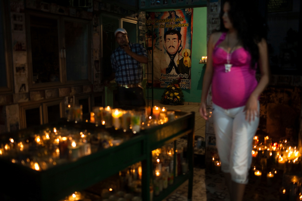 People paray at a chapel devoted to Jesus Malberde in Culiacan, Mexico.  Malverde is a folk saint worshipped by many people in the underworld and often associated with narcoculture and drug dealers. He is thought of as the Mexican version of Robin Hood, looking after those who have been forgotten by the Church and are involved in a life of crime.  People come to the chapel to show their respect and pray.