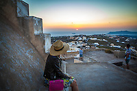 A woman enjoys the sunset in Pyrgos, Santorini, Greece