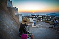 A woman enjoys the sunset in Pyrgos, Santorini, Greece