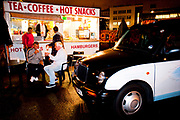 Taxi drivers at night taking refreshments, at an all night drinks and snacks cabin, in car park just off Brick lane, East London.