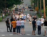 Spectators watch runner on Roosevelt Avenue during the 25th annual Orange Classic 10K road race in Middletown, N.Y., on June 11, 2005.
