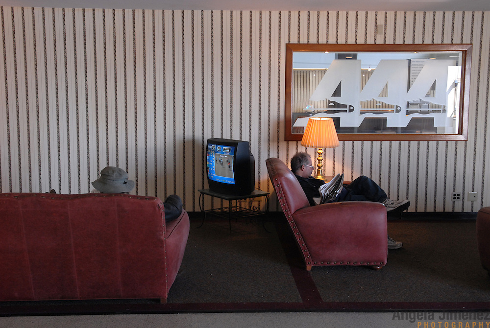 Betters sit in couches and watch races in the $2 admission Clubhouse area at the Aqueduct racetrack, which was renovated in 1959, on February 15, 2007...Betting on the horses is still a popular game and the money still flows, but off track betting and other forms of entertainment have eroded live attendance at the races.  The daily diehard betters and horse lovers who sparsely populate the place on work days are joined by a bigger crowd on the weekends. ..The Aqueduct, located in Ozone Park, Queens, is the only horse racing track in New York City and probably the coldest in the country (most of the others are in Kentucky, Florida or California). Horses race on the winterized inner dirt rack from January 1st through the end of April. Aqueduct was built in 1894, renovated in 1959, then opened for winter racing in 1975. It is the winter race track operated by the New York Racing Association (NYRA), which also runs Belmont and Saratoga in the warm seasons. Betters at Aqueduct watch and bet on the nine daily live races and all other races around the country via Simulcast. ..