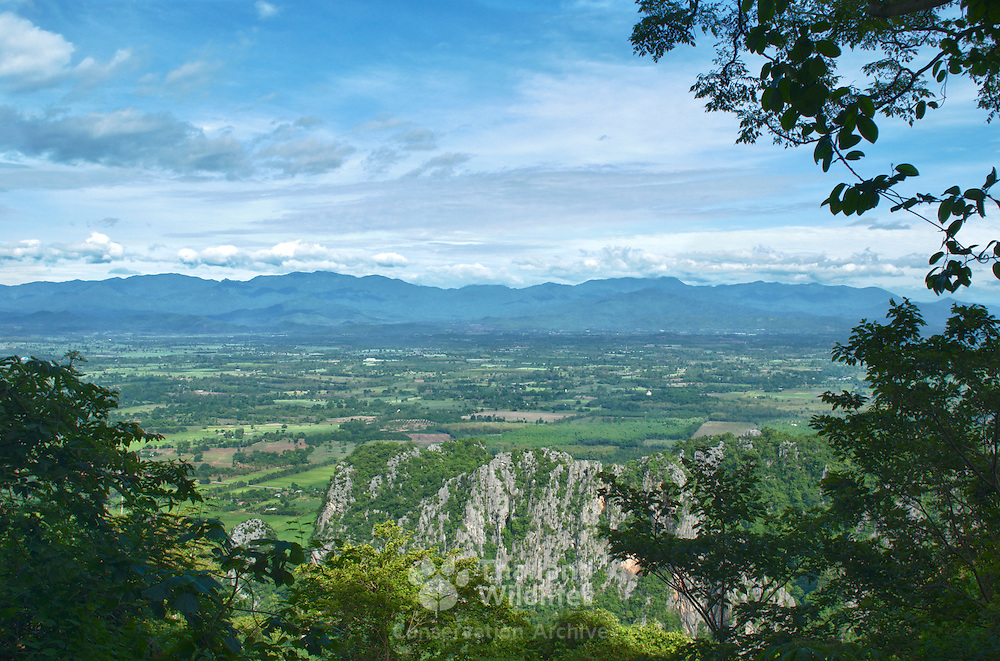 The mountains of the Huai Kha Kaeng Wildlife Sanctuary rise abruptly out the rural farming lands of Uthai Thani. View from atop a limestone karst in the province of Uthai Thani.