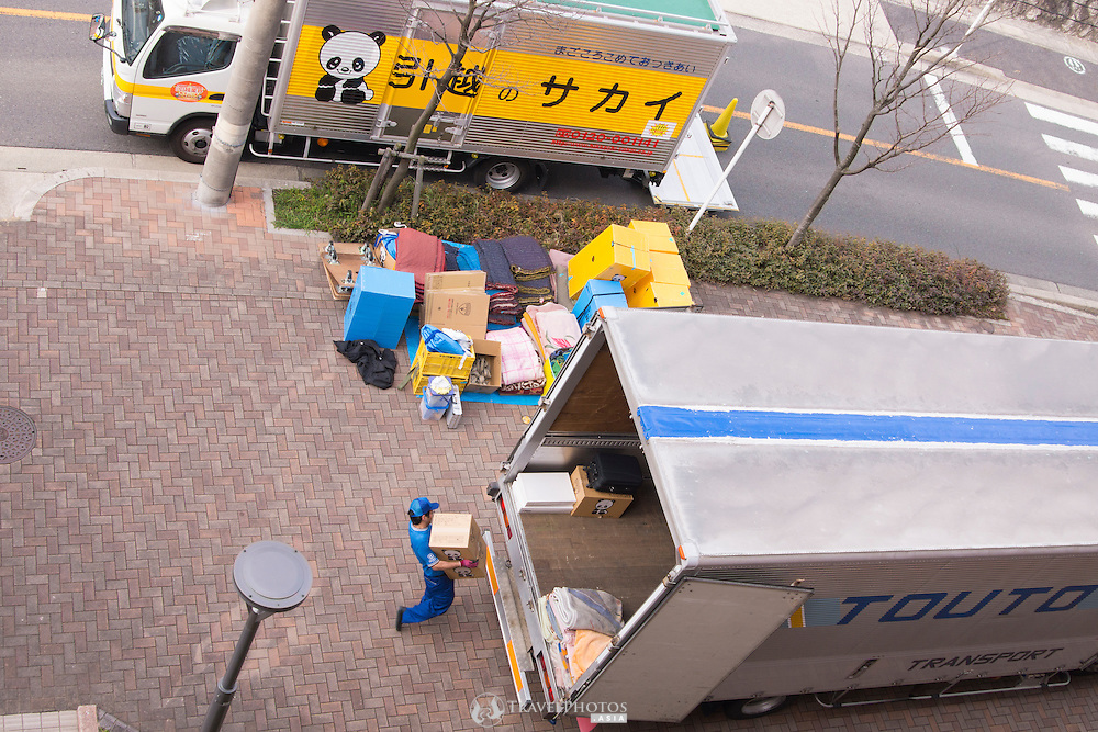 Removalists working in front of a condominium in moving season in Japan.
