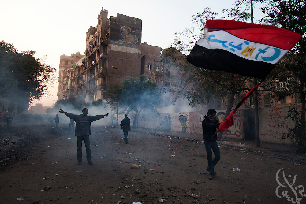 An Egyptian protestors defiantly wave an Egyptian flag as tear gas canisters fired by nearby security forces land behind during street battles November 21, 2011 near Tahrir square  in central Cairo, Egypt. Thousands of protestors demanding the military cede power to a civilian government authority clashed with Egyptian security forces for a third straight day in Cairo, with hundreds injured and at least 24 protestors killed.  (Photo by Scott Nelson)