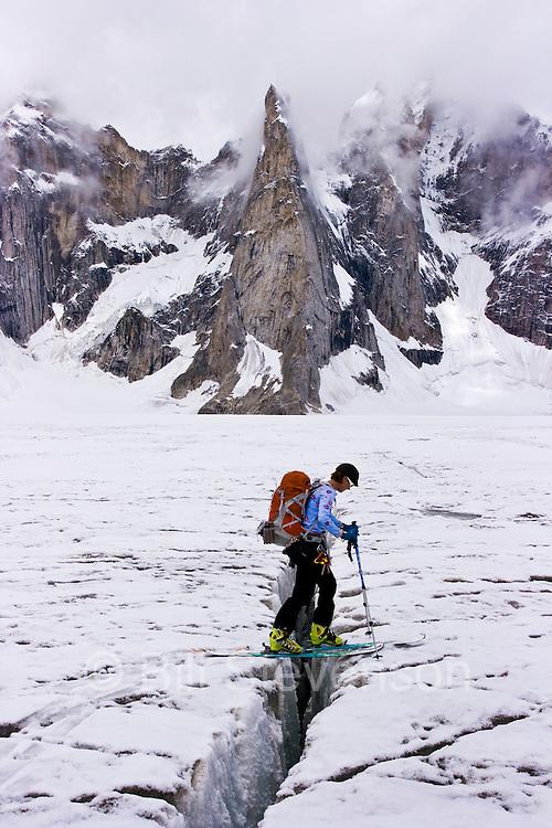 A woman ski mountaineer crossing a crevasse on the Biafo glacier in the Karakoram Himalaya in Pakistan