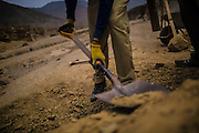 Patric, a Swedish volunteer digs for sand that will be used for natural construction in the desert of Cieneguilla, a quiet location in the outskirts of Lima, Peru, Friday, November, 13, 2015.