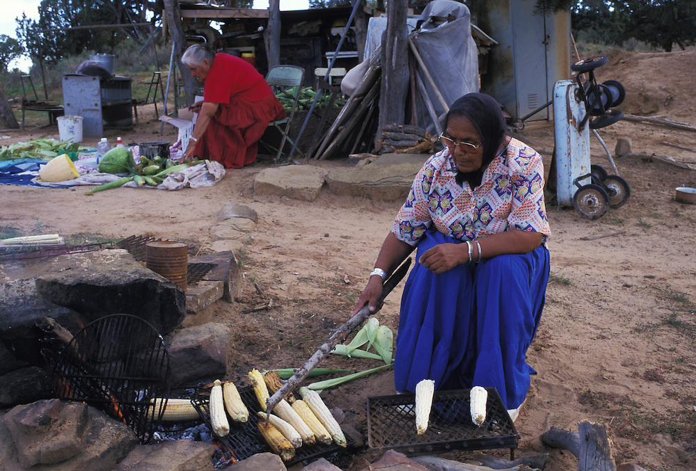 "Cooking - Lortia Addakai grills ears of corn as katherine Smith sorts through her field's harvest.  ""Our songs and our prayers are tied to this place,"" says Smith, who counts herself a resistor to relocation."