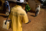 A health worker carrying polio vaccines walks through the village of Wantugu, northern Ghana, during a national polio immunization exercise on Friday March 27, 2009.