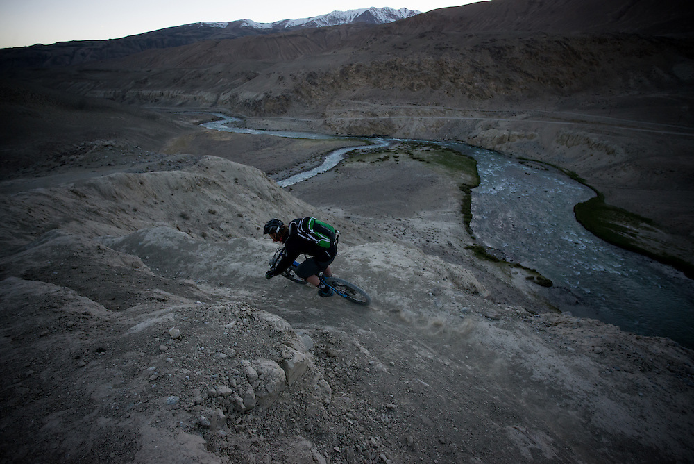 Within sight of the Tajik border on the other side of the Wakhan river, Matt Hunter rails another corner in our 12-day long singletrack loop. We would parallel this river and border for 2 days before veering away from it and finishing our ride. It would then be another 2 day drive to reach Tajikistan again. So near, yet so far.